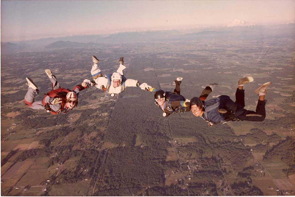 Skydivers. 4 women holding hands and smiling