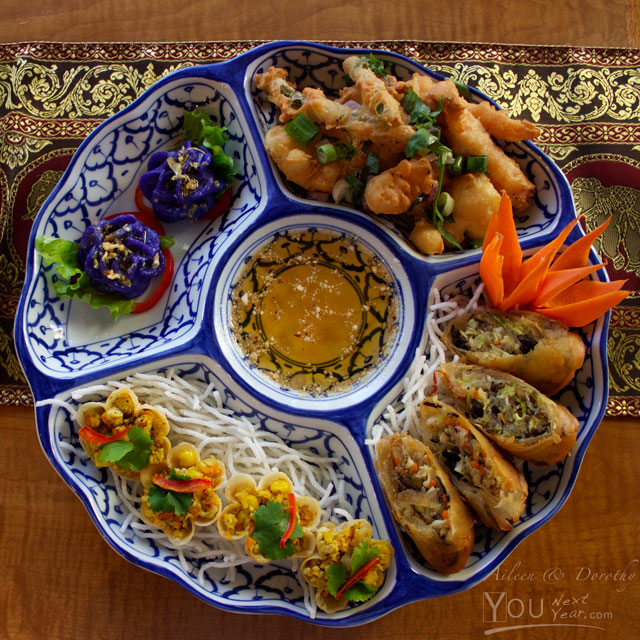 Appetizers at SalaThai: Golden Baskets, Flower Dumplings, Spring Rolls, Crispy Squid on hand-painted Thai dish, against Thai gold thread & red table runner