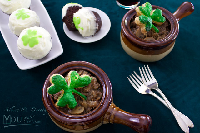 Guinness steak & onion stew in ramekins for 2 with green shamrock puff pastry tops. For dessert, mini Guinness chocolate cupcakes frosted with cream icing and green shamrock decoration. Glass of Guinness beer in the background.