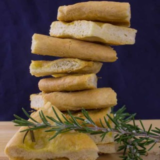 Rosemary focaccia sprinkled with truffled salt, fresh from the oven. Stacked high on wooden board.