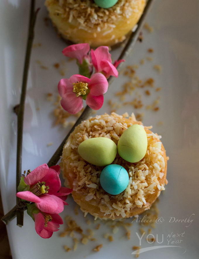 Mini cheesecakes topped with little coconut nests for Easter. Garnished with quince flowers.