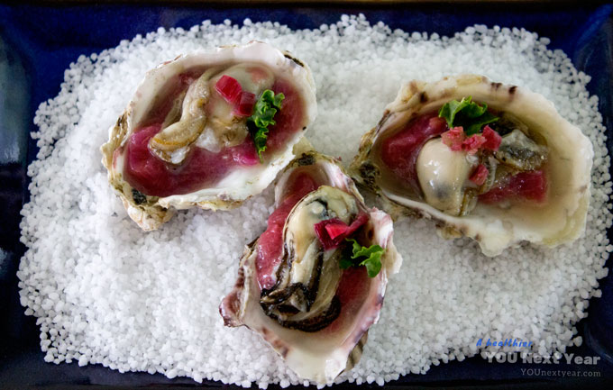 Three little ocean-fresh oysters with savoury rhubarb, shallot and ginger. On the half-shell and sitting on coarse salt.