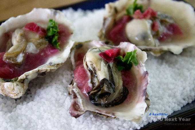 Royal Miyagi oysters with rhubarb, shallot & ginger compote on the half shell, freshly harvested from the coast of British Columbia. Sitting on bed of coarse salt.