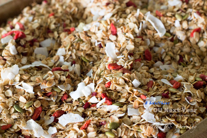 Baking pan filled with toasted oat & kamut flakes, coconut ribbons, Goji berries, pepitas, sunflower seeds for Homemade Granola