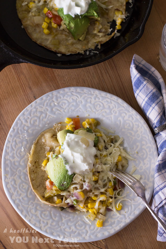 """Open-faced enchilada with grated cheese, """"sour cream"""", avocados, diced red onions and tomatoes."""