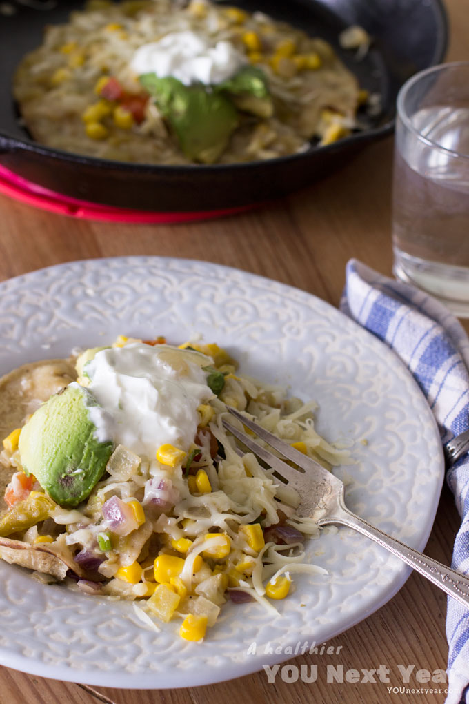 "Open-faced enchilada with grated cheese, ""sour cream"", avocados, diced red onions and tomatoes. In the background, a cast iron frying pan with your next warm enchilada."