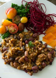Four colours of beans baked with molasses, onions, beer, apple cider vinegar, mustard and oregano. On plate with multi-coloured vegetables: red beets, carrots, kale, baby tomatoes