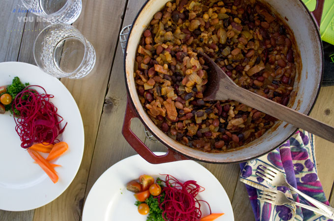 Ready to serve up quick, from scratch baked beans! Dutch oven full of baked beans and plates with colourful veggies.