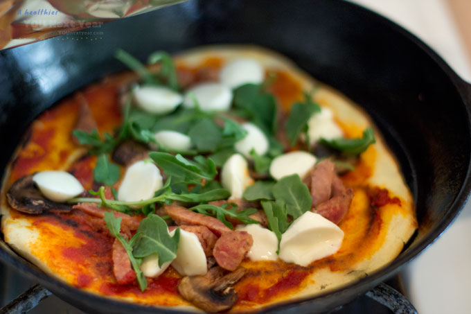 Crispy, chewy stove-top pizza with garlic-olive-oil-tomato sauce over from-scratch crust. Topped with fresh bocconcini, arugula, pan-fried mushroom, and sausage. In cast iron frying pan on the stove.