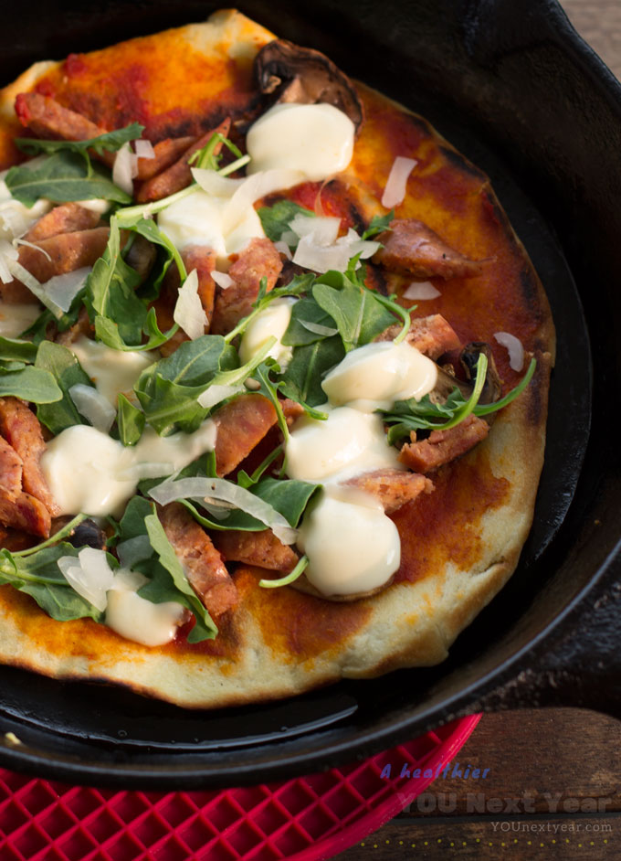 Melted bocconcini and thinly sliced onions mixed with arugula and sausage over crispy, chewy, from-scratch crust and garlic, tomato and olive oil sauce. In hot cast iron frying pan.