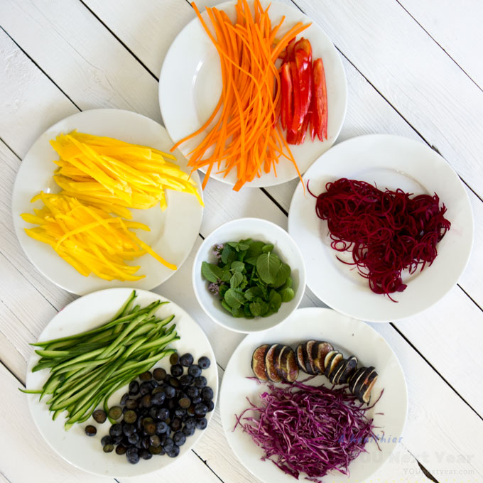 Ingredients for rainbow salad rolls. Red: beets & tomatoes. Orange: carrots. Yellow: sweet pepper & mango. Green: cucumber & mint leaves. Blue: blueberries. Violet: mission figs & cabbage. All vegetables sliced and arranged on white plates in a rainbow circle.