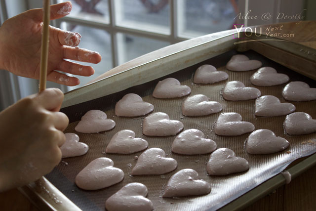 Aileen shaping heart-shaped, raspberyy macarons for Valentine's Day. Tray of pink hearts & sticky fingers