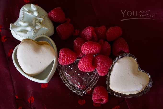 Heart-shaped raspberry macarons with vanilla-cream filling & scattered raspberries on deep red silk cloth