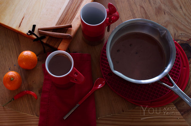 Mexican spiced hot chocolate half poured into red & silver cups with matching spoons. Vanilla, cinnamon, orange zest and red chilis scattered nearby. YOUnextYear.com
