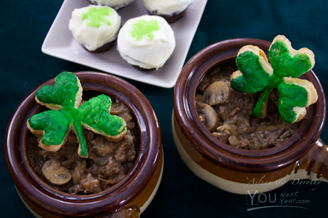Guinness steak & onion stew in ramekins for 2 with green shamrock puff pastry top, and mini Guinness chocolate cupcakes frosted with cream icing and green shamrock decoration.