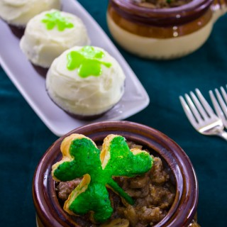 Guinness steak & onion stew with green shamrock puff pastry top in crockery ramekins, and Guinness chocolate cupcakes frosted with cream icing and green shamrock decoration.