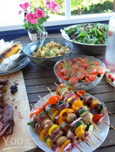 Potluck table laid outdoors on a perfect summer day: Sliced roast beef; barbecued corn on the cob; veggie shish kebabs; sweet tomatoes & dill salad; dark leafy greens salad; baby potatoes tossed in olive oil; cold water infused with raspberries & limes.