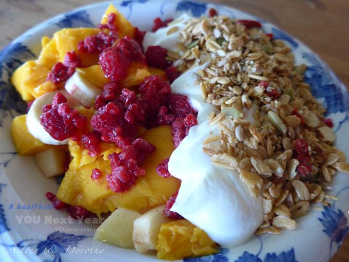 Juicy mango, apple, raspberries & bananas with plain yogurt with fresh, homemade granola