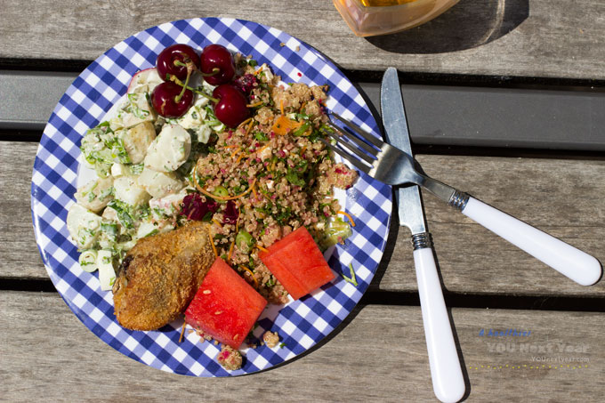 Picnic in the hot June sun. Potato salad, quinoa salad, baked chicken, watermelon and cherries. In blue gingham dish on weathered wood picnic table.