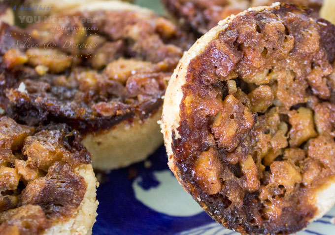 Sweet walnut topping on a plate of fresh butter tarts