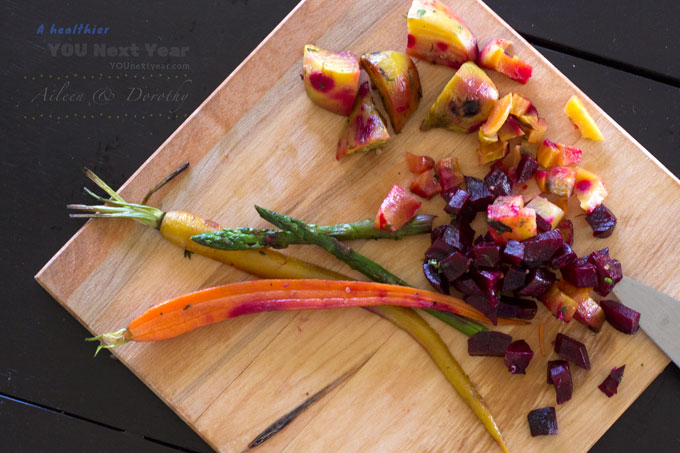 Sweet roasted beets, carrots and asparagus that were left over from Aileen's Father's & Grandpa's Day dinner. Roasted Veggies on chopping board with knife and measuring cup.