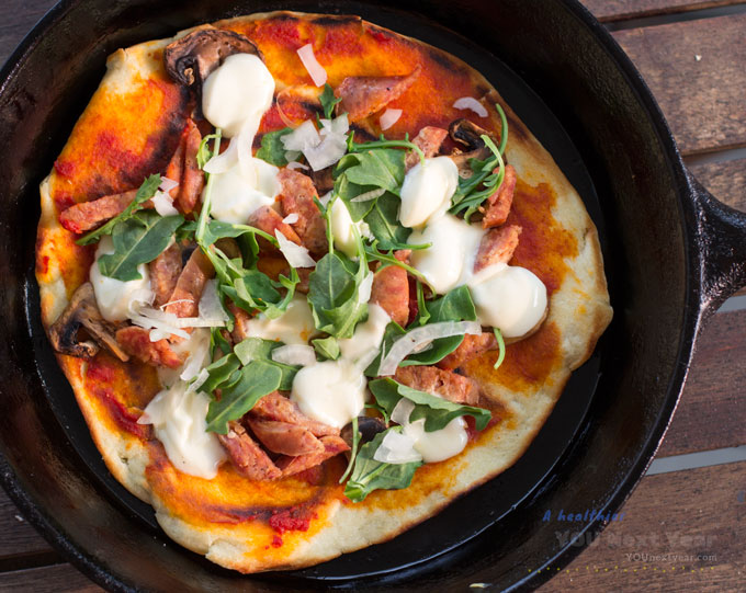 Hot stove-top pizza straight from the oven with melted bocconcini, arugula, thinly sliced pan-fried mushrooms, white onions and sausage. Garlic-olive-oil-tomato sauce. In cast iron frying pan.