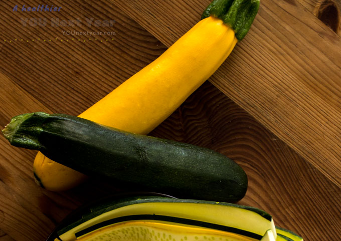 Yellow & Green Zucchinis and zucchini ribbons on plain wooden table