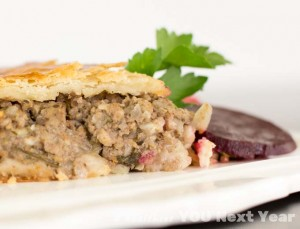 Tourtière closeup. You can see the flaky pastry and juicy meat