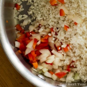 Finely chopped onions and red peppers with rice in a saucepan. Ready to sauté. Closeup.