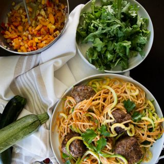 Big bowl of spaghetti & spiralized zucchini noodles tossed in romesco sauce. Salad fixings: bowl of barugula and bowl of chopped coloured peppers, fresh corn and red onion in rice vinegar soaked in mustard & olive vinaigrette