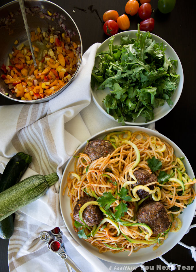 spaghetti & spiralized zucchini noodles tossed in romesco sauce, salad fixings: arugula, chopped coloured peppers in rice vinegar & olive vinaigrette