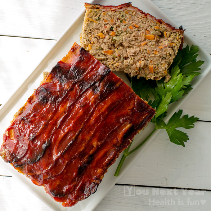 Red salty, sweet caramelized topping on meatloaf slice with bits of carrots and onion. Over fresh Italian parsley sprig.