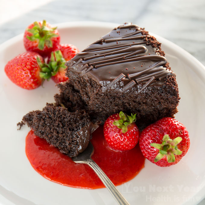 Forkful of moist chocolate cake with whole Vancouver strawberries and strawberry purée.