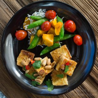 Bright sautéed cherry tomatoes, squash and sugar peas with crispy tofu topped with chiles and roasted peanuts.