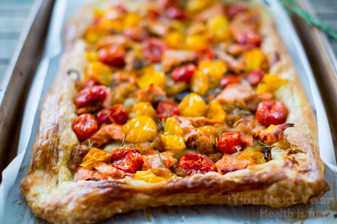 Caramelized yellow and red cherry tomatoes dotted with salmon and rosemary on flaky, crispy puff pastry.