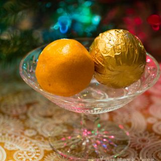 chocolate orange with real orange in crystal dish in front of christmas tree lights