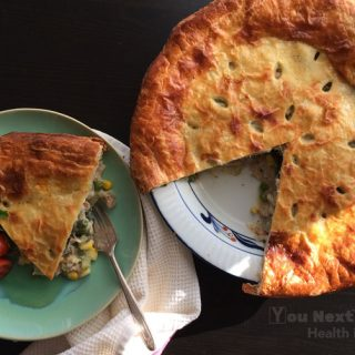 Overhead shot of chicken veggie pie with crispy, golden puff pastry top. Slice of pie with veggies spilling out on left with tarnished silver fork and red cherry tomato and flat-leaf parsley garnish. Whole pie with one slice cut out on right side with ray of sunshine highlighting the golden crust.