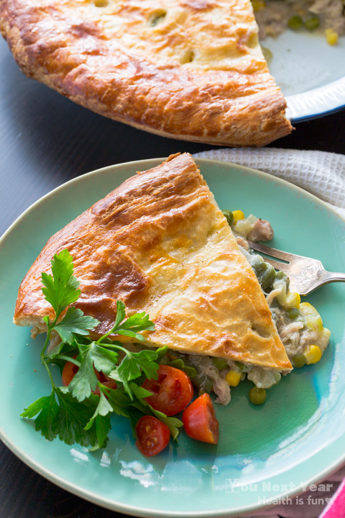 Slice of chicken veggie pie with crispy golden pastry top and veggies spilling out in foreground with tarnished silver fork and red tomato and flat-leaf parsley garnish. Whole pie with one slice cut out in the background.