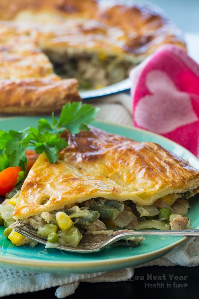 slice of chicken veggie pie with crispy, golden pastry top and veggies spilling out in foreground with tarnished silver fork and red tomato and flat-leaf parsley garnish. Red and pink heart linen in mid-ground side. Crispy pie with one slice cut out in the background.