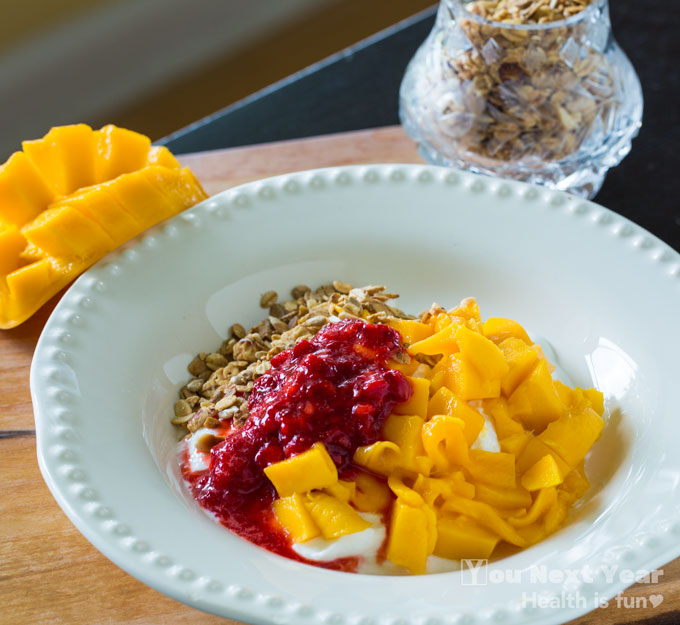 ivory earthenware bowl filled with raspberry sauce and pieces of mango. Sprinkled with Dorothy's granola. Scored mango on the side over cutting board. Small crystal pot of Dorothy's granola in background.