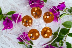 maltesers and tiny chocolate balls suspended in kahlua and orange liqueur jello shot circles, topped with little gold stars. on little crystal dish, surrounded with magenta bougainvillea, on white bamboo pattern tablecloth