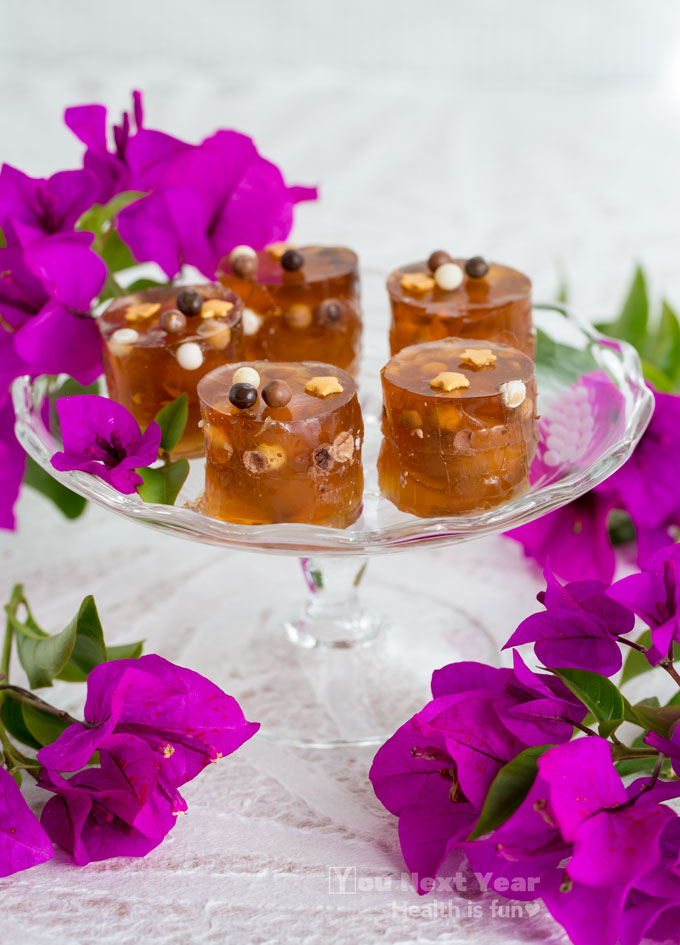 maltesers and tiny chocolate balls suspended in kahlua and orange liqueur jello shot cylinders, topped with little gold stars. on little crystal stemmed dish, surrounded with magenta bougainvillea blossoms, on white bamboo pattern tablecloth