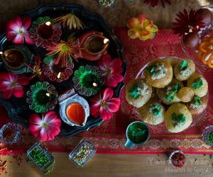 Diwali treats laid out on red tablecloth emboridered with gold thread. Painted little clay pot candles filled with oil surrounded by mums and silk flowers. Crispy pani puri bites stuffed with chickpea masala potatoes and tamarind masala water on the side. Indian sweets like gulab jamun and sugar-covered fennel in tiny crystal pots.