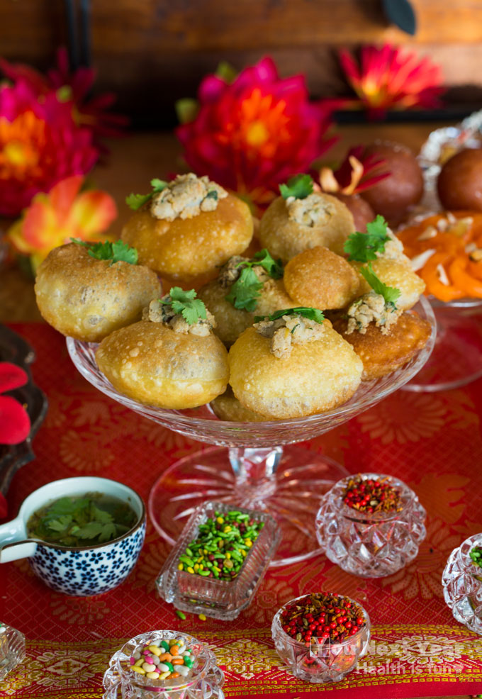 Crispy pani puri bites filled with chickpea masala potatoes with tamarind masala water. Red and yellow mums and silk flowers in the background. Candy-coated fennel seeds in red, green and mixed colours in tiny crystal bowls. Red and gold silk table cloth.