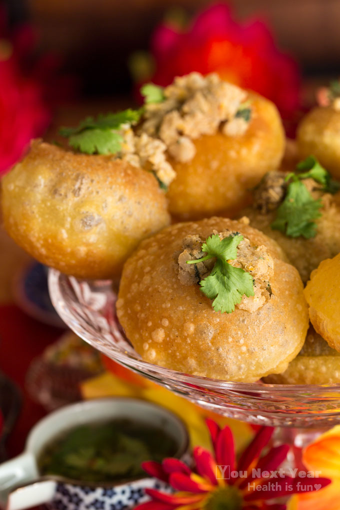 Closeup. Crispy pani puri bites filled with chickpea masala potoates in crystal stemmed dish. Tamarind masala water. Red and yellow mums and silk flowers in foreground and background.