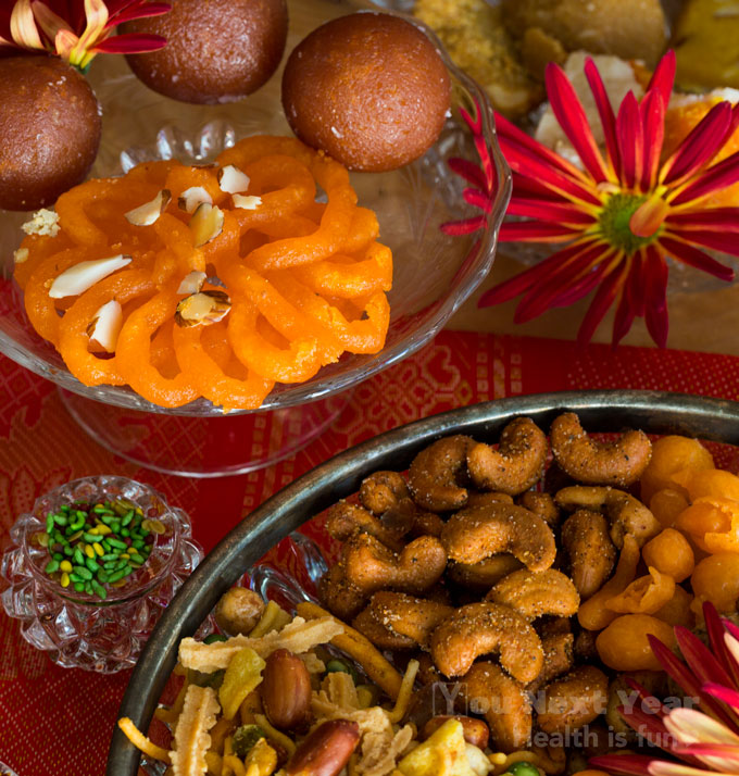 Diwali treats. Crispy saffron-coloured imarti and gulab jamun balls soaked in rose sugar syrup. Bright sugar-coated fennel seeds. Plate of spicy roasted cashews tossed in chili or citrusy salt. Crunchy savoury mix with giant peanuts and crisp chickpea-flour bites on red tablecloth shot with gold thread.