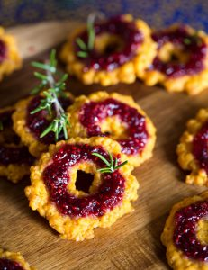 Crispy savoury cheese wreath cookie topped with raspberry preserves and rosemary sprigs on wooden board.
