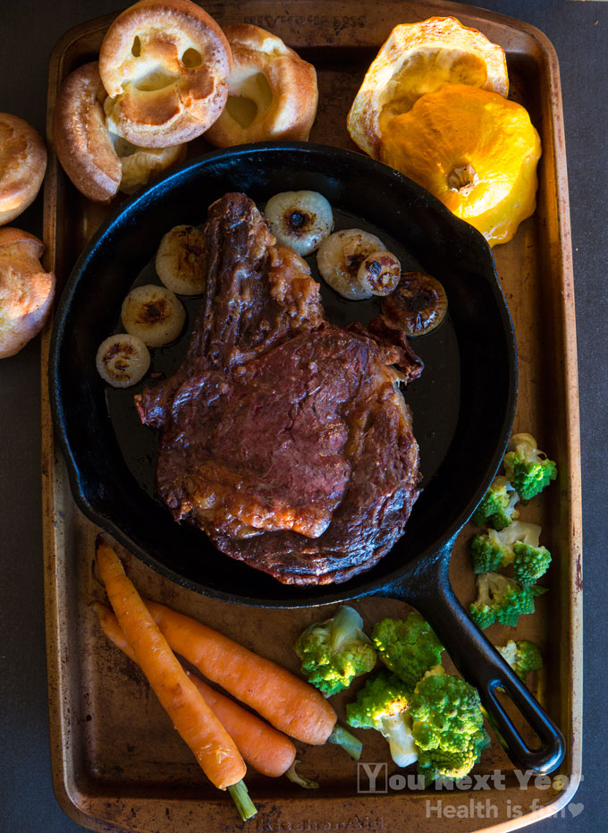 Standing rib roast, medium rare circled with little roasted cipollini onions on cast iron frying pan. Surrounded with Yorkshire pudding, yellow patty pan squash, Romanesco broccoli/cauliflower, and sweet orange carrots on roasting sheet.