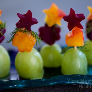 Row of gold and red, lightly pickled beet appetizers cut in stars, flowers and hearts with dill garnish - stacked and standing upright atop jumbo green grapes. Sitting on handmade pottery dish.