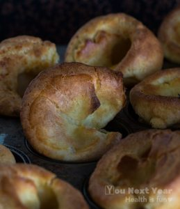 Closeup of warm, fragrant Yorkshire puddings in muffin tin. You can see the crispy golden outside crust and hints of the soft, chewy inside.